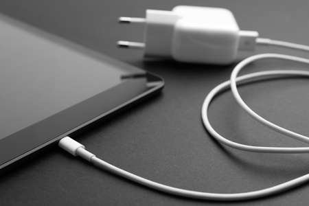 Tablet and charger on black background, closeup. Modern technology