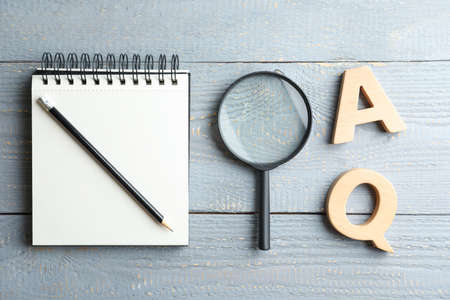Flat lay composition with notebook, magnifier glass and letters on light gray wooden table. Find keywords concept