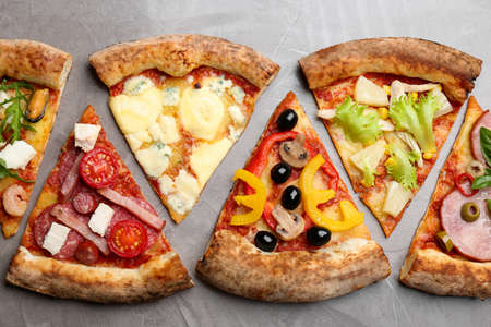 Slices of different delicious pizzas on gray table, flat lay Stock Photo