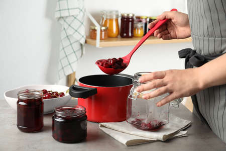 Woman making pickled cherries at table indoors, closeup