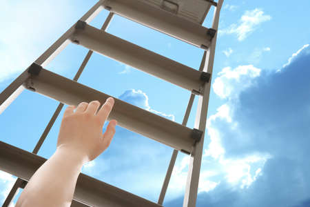 Woman climbing up stepladder against blue sky with clouds, closeup