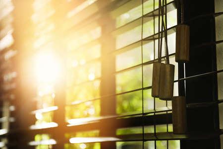 Sun shining through window with blinds in morning, closeup