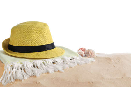 Folded towel, hat and shells on sand against white background, space for text. Beach objects
