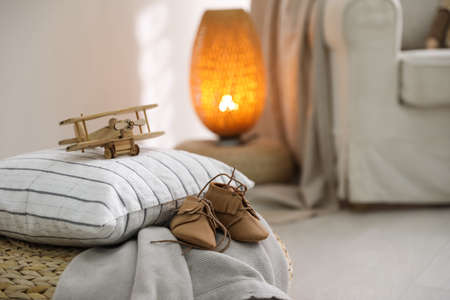Wooden airplane and cute child's boots on pouf in baby room, closeup. Space for text
