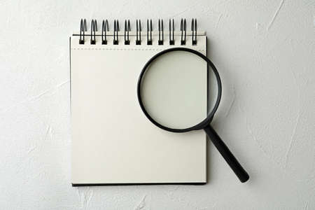 Magnifier glass and empty notebook on white stone background, flat lay with space for text. Find keywords concept