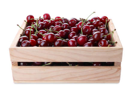 Sweet juicy cherries in crate on white background