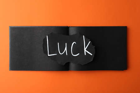 Sheet of paper with word LUCK and notebook on orange background, top view