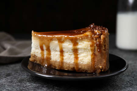 Piece of delicious cake with caramel served on gray table