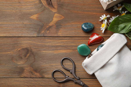 Flat lay composition with different gemstones and healing herbs on wooden table, space for text
