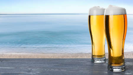 Cold beer on wooden desk against blurred sea. Space for text