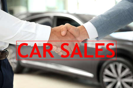 Young salesman shaking hands with client in car dealership, closeup Stockfoto