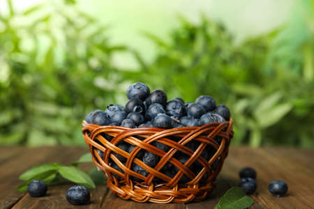Tasty ripe blueberries in wicker bowl on wooden table Standard-Bild