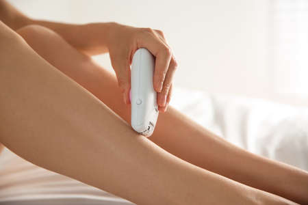 Woman doing leg epilation procedure on bed, closeup Foto de archivo