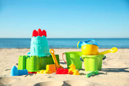 Different child plastic toys on sandy beach