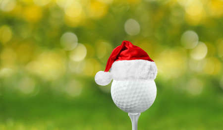Golf ball with small Santa hat on tee against blurred background Foto de archivo