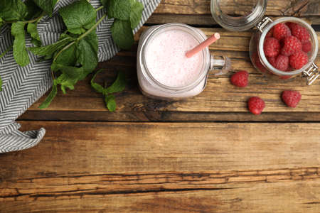 Tasty milk shake with raspberries and mint on wooden table, flat lay. Space for text Standard-Bild