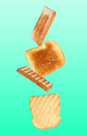 Tasty toasts falling on color background Standard-Bild