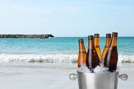 Bottles of beer with ice cubes in metal bucket against ocean and sandy beach. Space for text Reklamní fotografie
