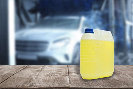 Plastic canister with cleaning liquid for vehicle on wooden surface at car wash. Space for text Stock Photo