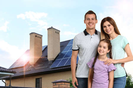 Happy family near their house with solar panels. Alternative energy source