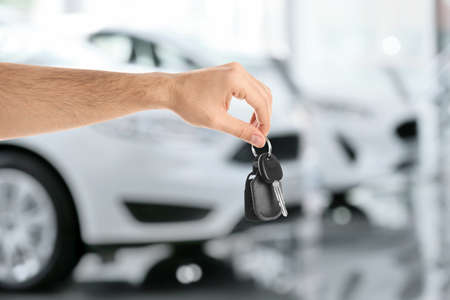 Car buying. Man holding key against blurred automobiles, closeup