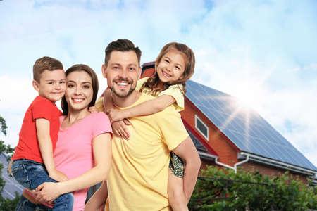 Happy family near their house with solar panels. Alternative energy source