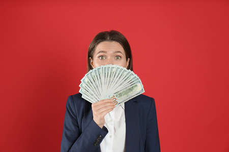 Young woman with money on crimson background
