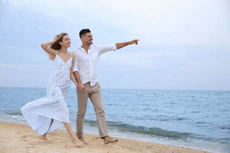 Happy couple having romantic walk on beach. Space for text Foto de archivo