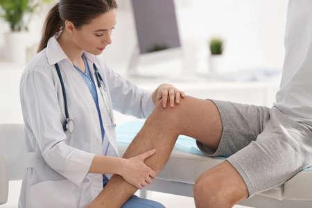 Female orthopedist examining patient's leg in clinic, closeup