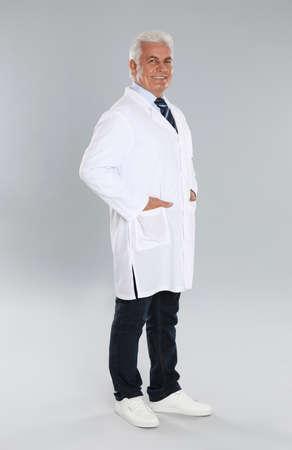 Happy senior man in lab coat on light gray background