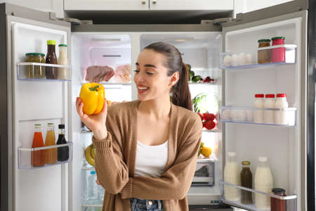Young woman with bell pepper near open refrigerator Imagens