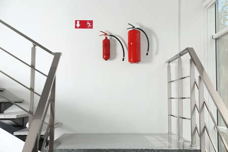 Fire extinguishers and emergency exit sign on white wall near staircase indoors