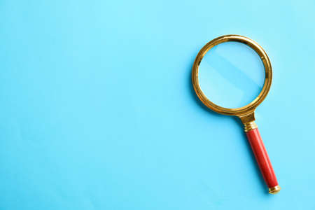 Top view of magnifier glass on light blue background, space for text. Find keywords concept 스톡 콘텐츠