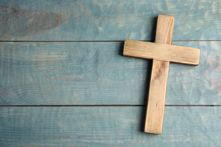 Christian cross on light blue wooden background, top view with space for text. Religion concept