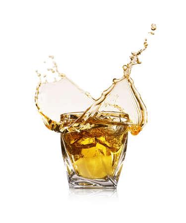 Whiskey splashing in glass on white background Stock Photo