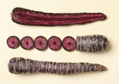 Whole and cut raw purple carrots on beige background, flat lay