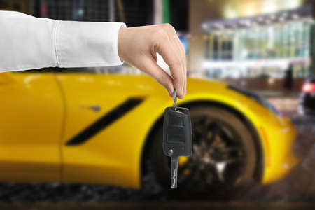 Car buying. Man holding key against blurred automobile, closeup