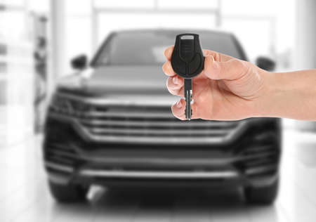Car buying. Woman holding key against blurred automobile, closeup