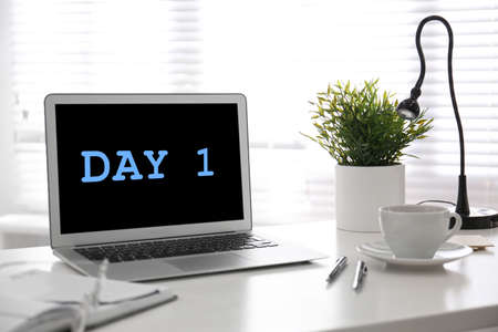 Start new job. Laptop with text Day 1 on screen in modern office 스톡 콘텐츠