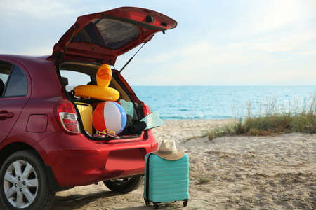 Red car luggage on beach, space for text. Summer vacation trip Stockfoto