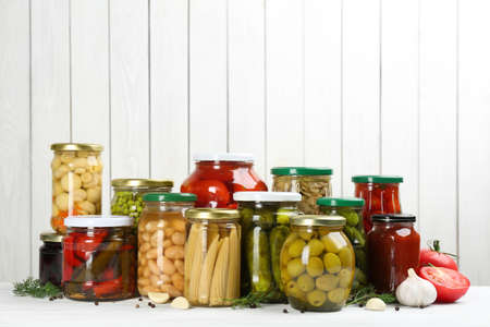 Glass jars with different pickled vegetables and mushrooms on white wooden background