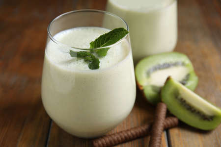 Tasty milk shake with kiwi on wooden table, closeup