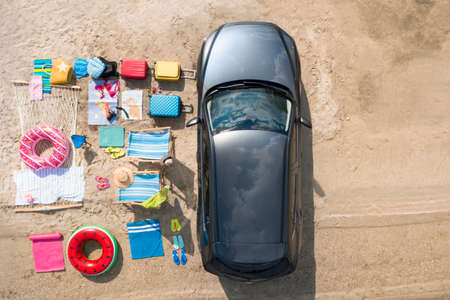 Car and beach accessories on sand, aerial view. Summer trip