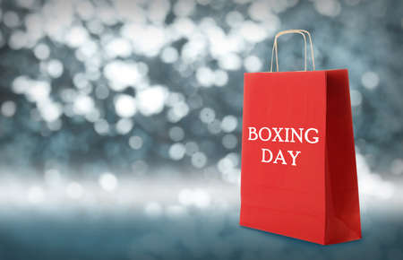 Red shopping bag with text Boxing Day on blurred background, closeup. Space for text