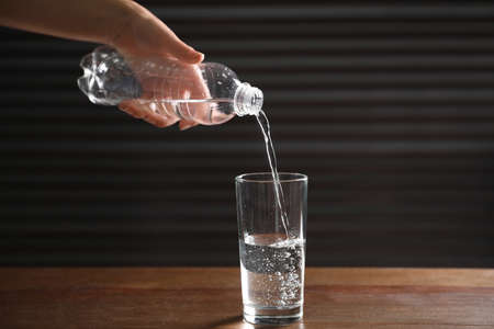Woman pouring water from bottle into glass on wooden table against dark background, closeup