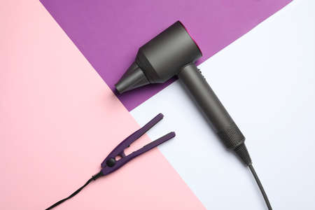Hair dryer and iron on color background, flat lay. Professional hairdresser tool