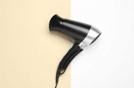 Hair dryer on color background, top view. Professional hairdresser tool