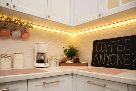 Stylish kitchen interior with modern coffeemaker on countertop