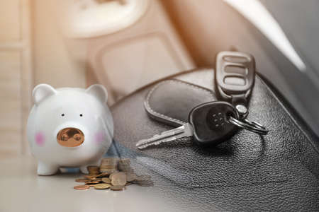 Buying vehicle. Double exposure of car key and piggy bank with coins Standard-Bild
