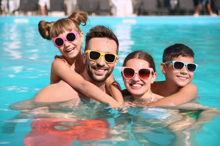 Happy family in swimming pool on sunny day Stockfoto